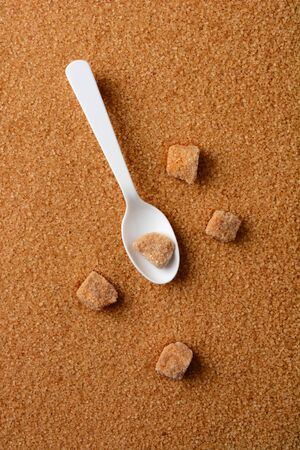 granulated: Overhead shot of lumps of raw brown sugar and a white spoon laying of a bed of granulated turinado sugar. Vertical format with copy space.