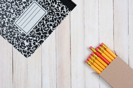 composition book: High angle shot of a box of pencils and a composition book on a white wood surface. Objects are in opposite corners of the frame. Stock Photo