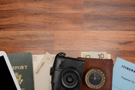 itinerary: High angle shot of a travel still life. Items include: passport post cards camera and itinerary. Horizontal format with copy space at the top. Stock Photo