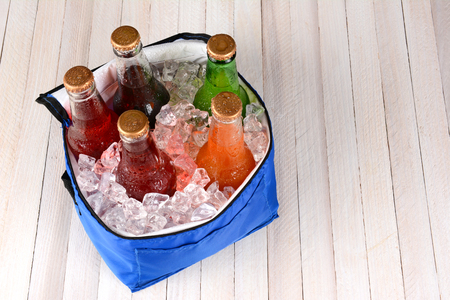 High angle shot of a collapsible cooler filled with crushed ice and soda bottles on a rustic wood picnic table. Horizontal format with copy space. Stock fotó