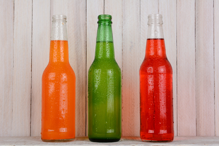 sodas: Three soda bottles on a wood background. The bottles are open and covered with condensation. Orange soda, Strawberry soda and Lemon Lime are represented.