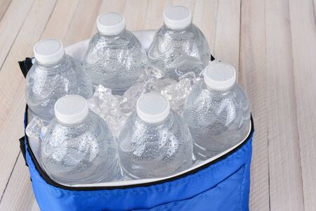 Closeup of six plastic water bottles and ice in a collapsable cooler on a white wood table. Horizontal format with copy space