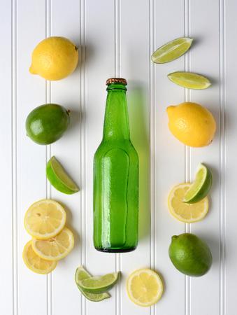 신선한 잘라 및 전체 레몬 및 라임에 둘러싸여 레몬 라임 소다 병의 높은 각도 샷입니다. 세로 형식입니다. 스톡 콘텐츠