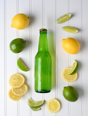 High angle shot of a bottle of lemon lime soda surrounded by fresh cut and whole lemons and limes. Vertical format.