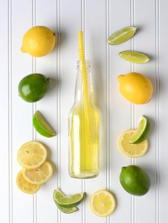 agua con gas: Las l�neas y los limones que rodean una botella de soda en una tabla tablero del grano blanco. Alto �ngulo de disparo en formato vertical. Foto de archivo