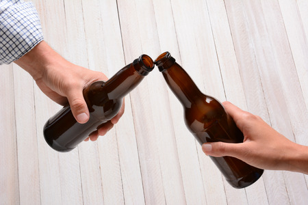 clinking: A man and a woman toasting with beer bottles. They are clinking the bottle tops over a rustic wood .
