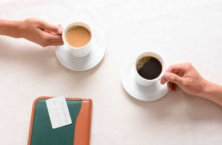 coffee table: A man and woman reaching for their coffee cups across a cafe table. Overhead closeup with only the peoples hands being shown.