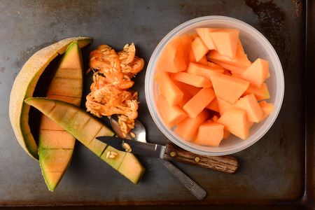 rinds: High angle shot of a bowl full of cantaloupe pieces next to the rinds and seeds. A knife and spoon are also on the metal kitchen surface. Stock Photo