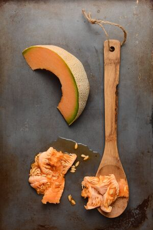 high angle shot: High angle shot of a cantaloupe slice next to a wooden spoon and the seed pulp. Overhead view in vertical format.