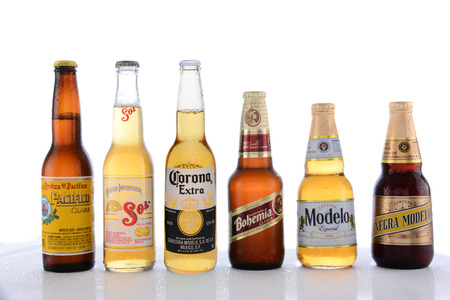 sol: IRVINE, CA - JUNE 14, 2015: Popular Mexican Beers. Pacifico, Sol, Corona, Bohemia and Modelo beer bottles on a wet table with reflections.
