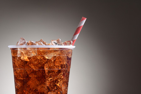 red cup: A clear plastic cup filled with ice and cola. Only half the cup is shown with a red and white striped straw over a light to dark gray background. Stock Photo