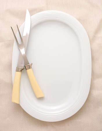 A carving knife and fork on a platter, the platter is oval and white. The carving set has bone handles and the background surface is also off-white. High angle in vertical format. 版權商用圖片 - 41385438