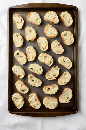 spread sheet: A baguette sliced and spread out on a baking sheet in preparation for toasting. Overhead view in Vertical format.
