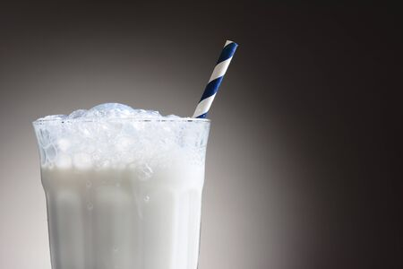 Closeup of a cold glass of milk with a blue and white striped drinking straw. The milk glass has a frothy top with bubbles running down the outside. Horizontal over a light ot dark gray background.