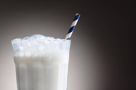 verre de lait: Gros plan d'un verre de lait froid avec une paille rayée potable bleu et blanc. Le verre de lait a un top mousseuse avec des bulles qui descend l'extérieur. Horizontal sur un fond gris foncé ot lumière. Banque d'images