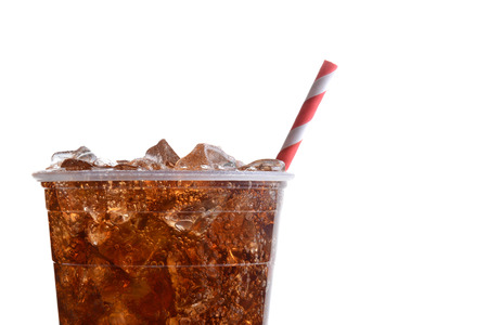 sodas: Closeup of a plastic cup filled with ice and cola. Only half the cup is shown with a red and white striped straw over a white background.