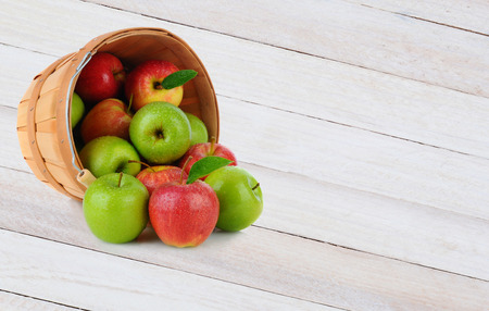 granny smith: High angle shot of a basket full of Gala and Granny Smith apples spilling out onto a rustic wood surface.