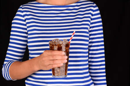 sodas: Closeup of a girl holding a cold glass of soda in front of her torso. A red a white striped straw is in the glass and the unrecognizable female is wearing a blue striped blouse. Stock Photo