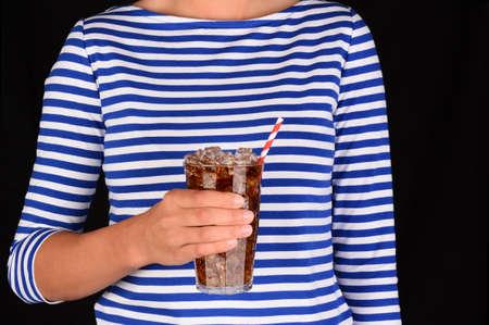 gaseosas: Primer plano de una niña sosteniendo una copa fría de refresco frente a su torso. A una paja blanco a rayas de color rojo se encuentra en el vidrio y la hembra irreconocible lleva una blusa a rayas azul.