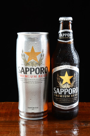 sapporo: IRVINE, CA - JUNE 18, 2015: A can and bottle of Sapporo Beer on a wet bar. The Japanese brewery founded in 1876 by German trained brewer Seibei Nakagawa is the oldest beer brand in Japan.
