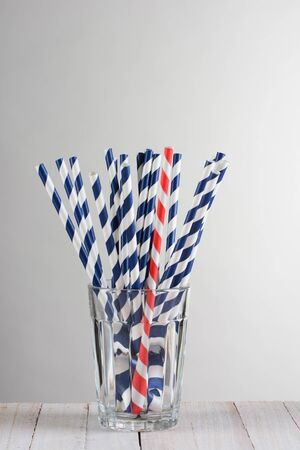 One red striped drinking straw mixed in with a bunch of blue striped straws. The straws are fanned out in a drinking glass on a wood table against a light to dark gray background.