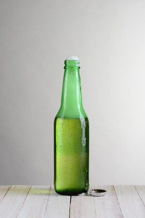 slant: One green beer bottle on a wood table against a light to dark gray background. The bottle is open with foam coming out the open top. Vertical format with copy space. Stock Photo