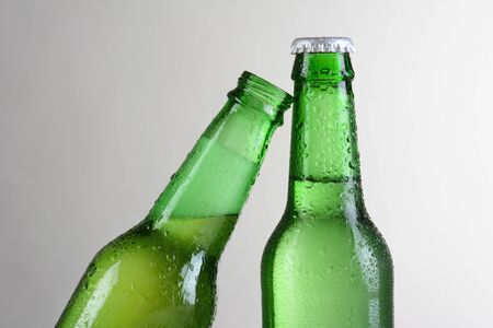 slant: Closeup of two green beer bottles against a light to dark gray background. One bottle is at a slant leaning on the other bottle. Horizontal format with copy space.