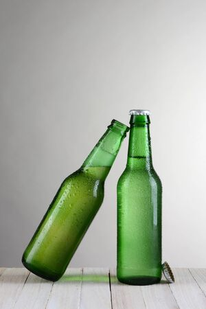 slant: Two green beer bottles on a wood table against a light to dark gray background. One bottle is at a slant leaning on the other bottle. Vertical format with copy space.