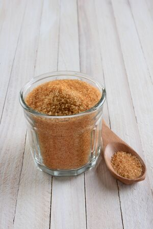 high angle shot: High angle shot of a glass bowl full of granulated brown sugar on a rustic whitewashed wood table. A wood spoon is laying next to the bowl. Stock Photo