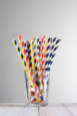 fanned: A bunch of multi-colored drinking straws .The straws are fanned out in a drinking glass on a wood table against a light to dark gray background.