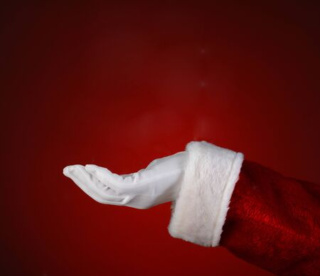 st nick: Santa Claus hand with his palm facing up over a light to dark red background. Closeup showing only his hand and arm.
