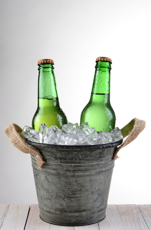 beer bucket: An old fashioned bucket with two beer bottles. Vertical format on a light to dark gray background with copy space. Stock Photo