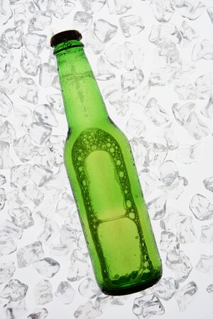 no label: A single green bottle of beer backlit on a bed of ice. The bottle has no label. Vertical Format.