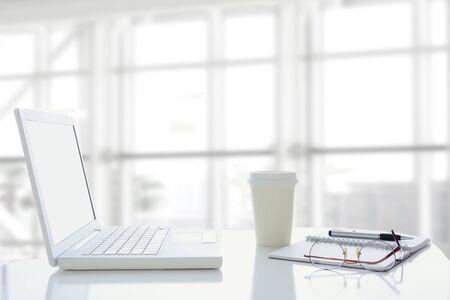 articulos oficina: Un ordenador portátil abierto en la ventana de la oficina moderna. La ventana está fuera de foco y de alta clave. Escritorio también tuvo taza de café desechables, un bloc de notas y gafas.