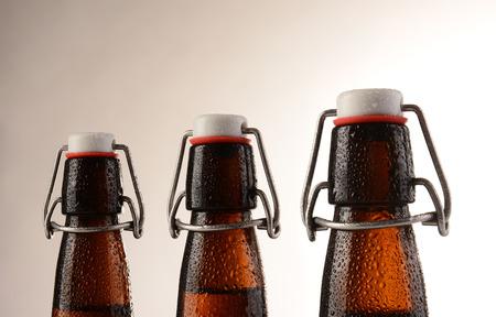 condensacion: Tres botellas de cerveza pivotar superiores cubiertas de condensaci�n. Formato horizontal con una luz c�lida a fondo oscuro.