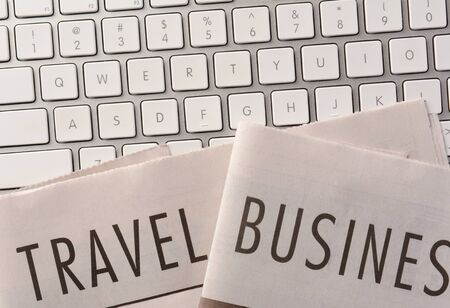 high angle: The Travel and Business Sections of a newspaper on a computer keyboard. High angle closeup in horizontal format. Stock Photo