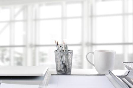 office desk: Closeup of a business desk in front of a large modern office window. The window is out of focus and high key. All items are white or silver.