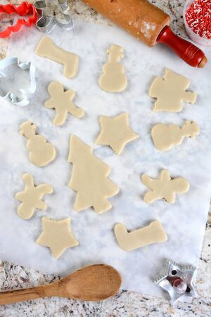perimeter: Christmas Cookie shapes on parchment paper. Around the perimeter are cutters, tub of sprinkles, spoon and rolling pin. Vertical format from a high angle. Stock Photo