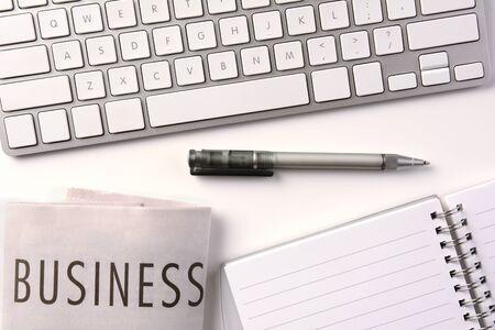 pad pen: Alto �ngulo de disparo de un escritorio con la secci�n de negocios del peri�dico, una almohadilla, pluma y el teclado del ordenador. Todos los art�culos son tonos de blanco o de plata.