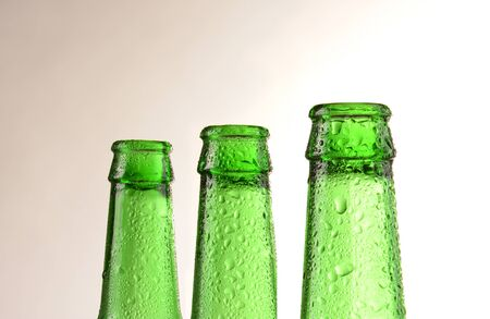 condensacion: Three green beer bottles covered with condensation. Horizontal format with a warm light to dark background. Foto de archivo