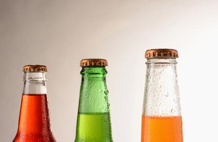 lima limon: Tres botellas de soda diferentes cubiertas de condensaci�n. Formato horizontal con una luz c�lida a fondo oscuro. Las sodas son; Fresa, naranja y lim�n
