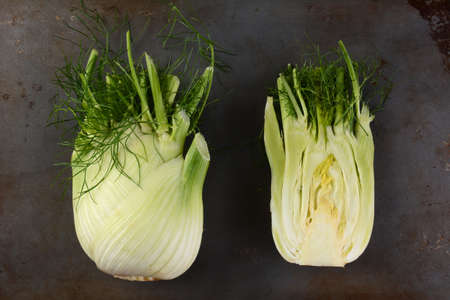 two and a half: High angle view of two fennel bulbs on a metal surface. One bulb is cut in half.