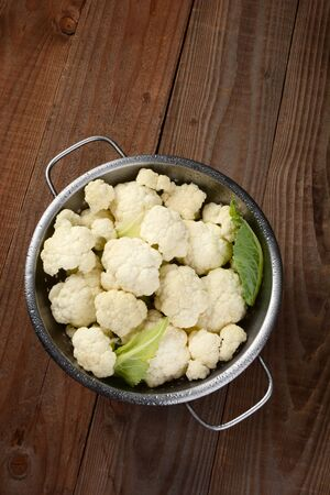high angle: High angle view of a colander filled with cauliflower florets. On a rustic wood table. Vertical format.