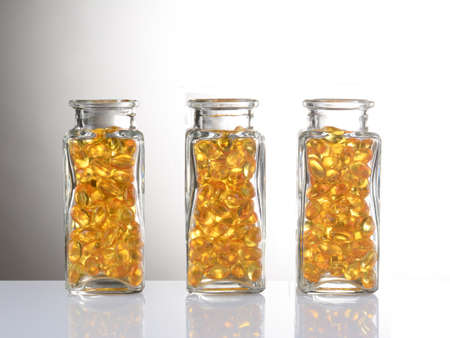 capsule: Three clear bottles filled with yellow capsules. On a white table with reflection and a light to dark gray background.