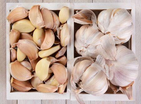 high angle view: High angle view of garlic bulbs and cloves in small white wood crates. Stock Photo