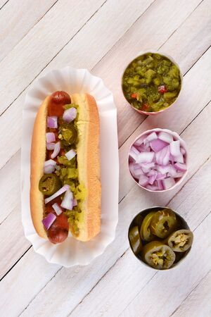 Overhead still life of a summer picnic table with a hot dog smothered in relish onions and jalapenos. Three cups of condiments are lined up next to the sandwich.