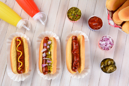 Overhead still life of a summer picnic table with hot dogs and condiments. Three franks in buns with ketchup, mustard, and relish surrounded by condiments.