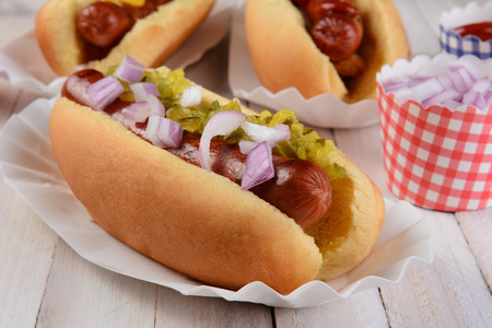 Closeup of a hot dog with relish and onions, in the background are two additional franks in buns and cups of condiments.