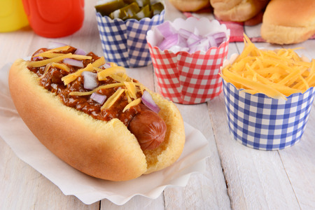 Closeup of a grilled chili dog with cheese and onions on a rustic wood picnic table. More buns and condiments fill the background.