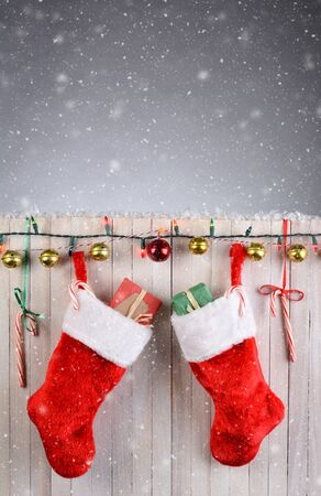 Two Christmas Stocking hanging on a rustic white fence with lights, jingle bells, and candy canes. Vertical format with snow effect.